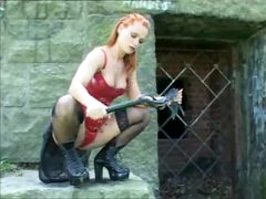 Gal in leather with a flogger outdoors