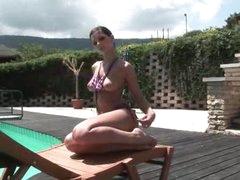 Chick in a bikini poses poolside